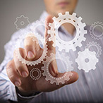 The workings of a business, represented by an executive touching gear graphics on a screen