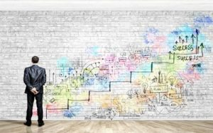 An executive looking at the path to success drawn as graffiti on a white brick wall