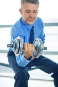 An executive lifting weights in a more physical strengths and weaknesses exercise