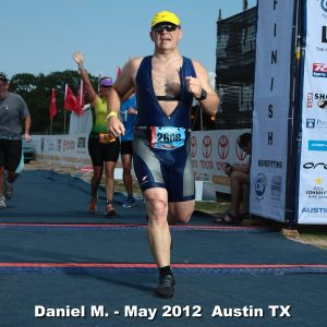 Daniel J. Mueller crossing the finish line at the Austin, Texas CapTex Triathlon while wearing a yellow Nike hat