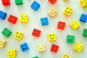 Colorful wooden cubes painted with expressive faces like a basic emotional intelligence test