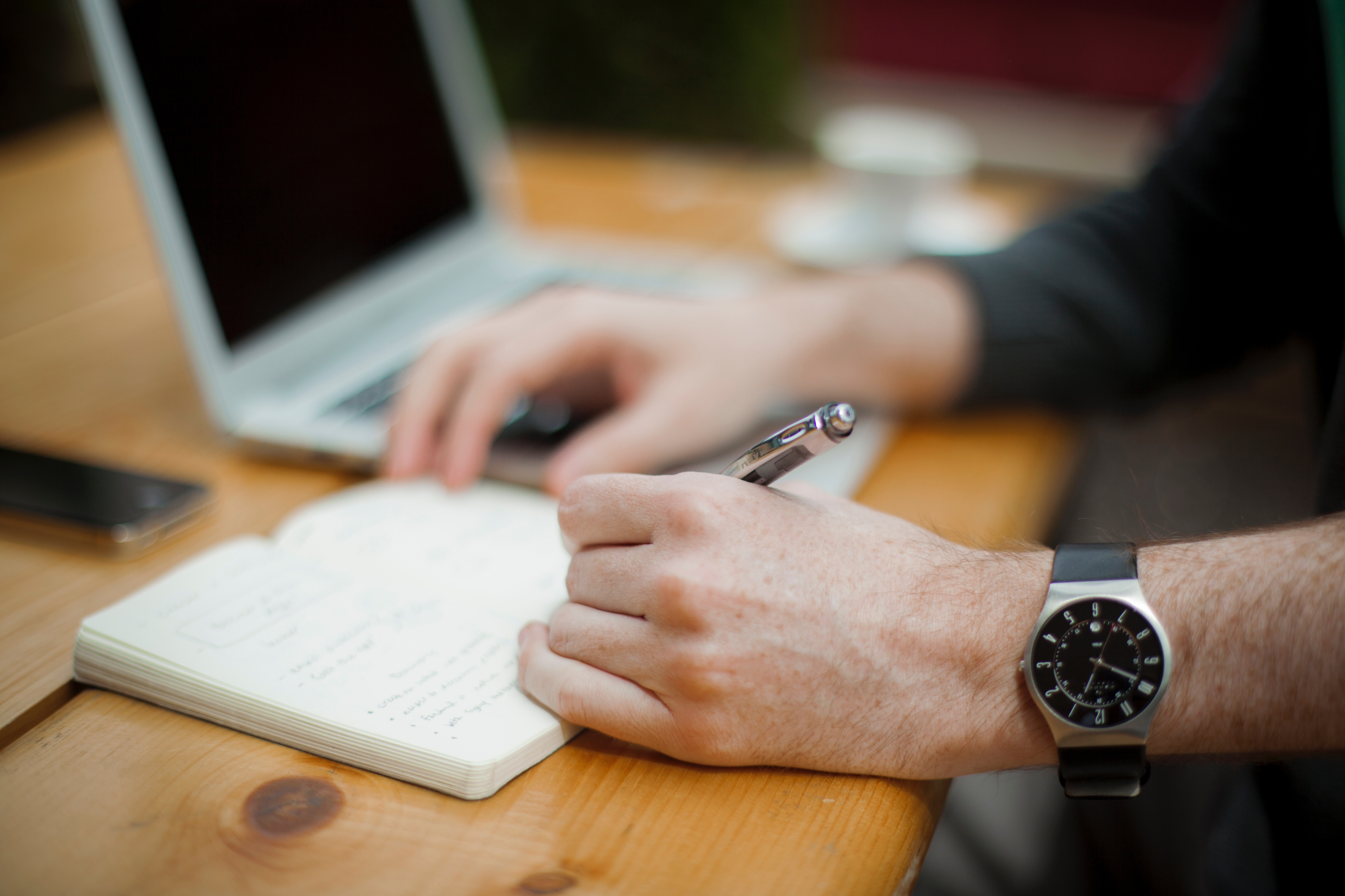 A close-up of a man's watch and hand as he's writing in a notebook, managing time and priorities