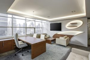 A well-organized office featuring modern design, white chairs and walls, and unique lighting